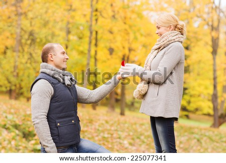 love, family, autumn and people concept - smiling couple with engagement ring in small red gift box outdoors - stock photo