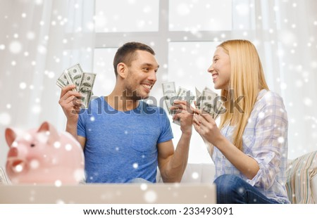 love, family, finance, money and happiness concept - happy couple with cash money and piggybank cheering at home - stock photo