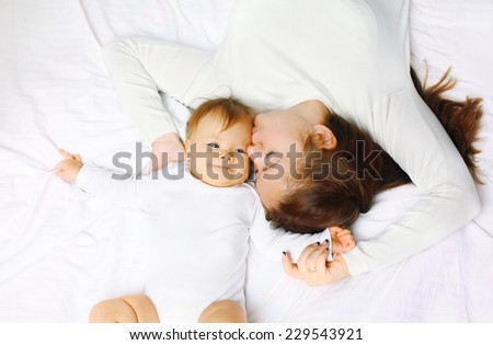 Love, family harmony concept - mother and baby lying on bed at home - stock photo