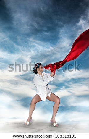 Love Flag/Pretty girl holding the red satin material flying in the wind. She is wearing curlers, white shirt and heels. Sky background - stock photo