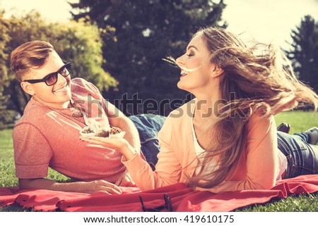 Love food and happiness. Smiling joyful cute couple on picnic in garden park. Happy lovers dating on fresh air. - stock photo