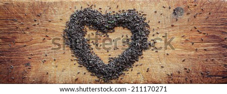 Love for caraway: carum carvi seeds arranged in heart shape on old wooden cutting board.  - stock photo