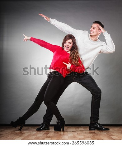 Love friendship and happiness concept. Smiling young couple having fun, happy man and woman studio shot on gray