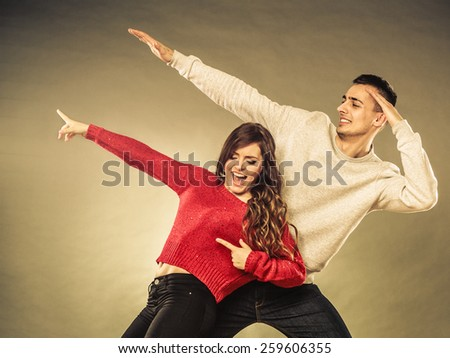 Love friendship and happiness oncept. Smiling young couple having fun, happy man and woman studio shot vintage filter - stock photo