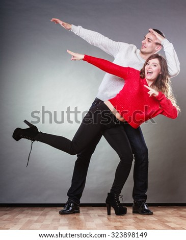 Love friendship and happiness oncept. Smiling young couple in full length having fun, happy man and woman studio shot on gray - stock photo