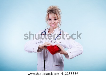 Love from working and helping people. Mid age blonde doctor in white medical apron with heart on blue. Enjoy work concept. - stock photo