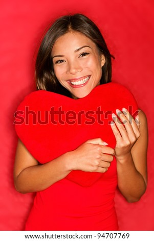 Love girl holding heart. Love concept photo with young woman in love holding red heart on red background. Multiracial asian caucasian valentines day woman.