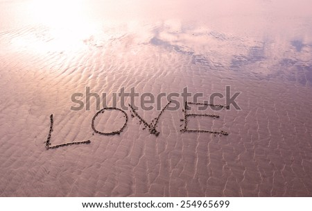Love handwritten in sand for natural, symbol,tourism or conceptual designs - stock photo