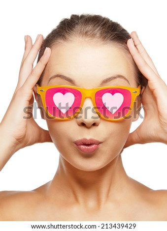love, happiness, valentines day, face expressions and people concept - portrait of surprised teenage girl in pink sunglasses with hearts - stock photo