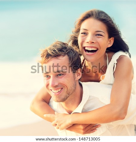 Love - Happy couple on beach having fun piggyback ride outdoor smiling happy laughing together on romantic holidays vacation travel trip. Young multiracial people, Asian woman, Caucasian man, 20s. - stock photo