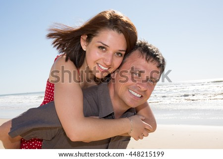 Love - Happy couple on beach having fun piggyback ride outdoor smiling happy laughing together on romantic holidays vacation travel trip.