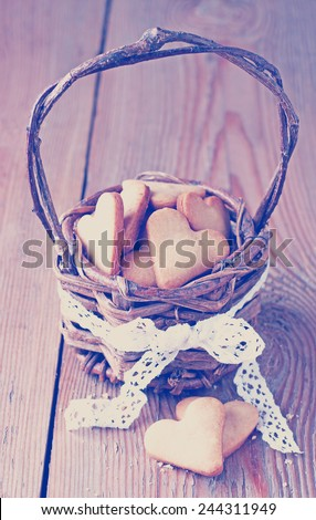 Love, happy, holiday, food, home, concept. Handmade heart cookies for Valentine's day in a basket on a wooden table. Vintage style. Toned image. Selective focus - stock photo