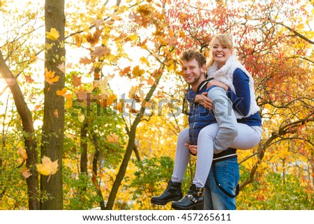 Love healthy relationship and dating concept. Lovers couple having fun, man giving piggyback to woman in autumn park. Young adults girlfriend and boyfriend hugging happy. - stock photo
