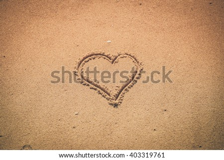 Love heart drawn on sand background texture