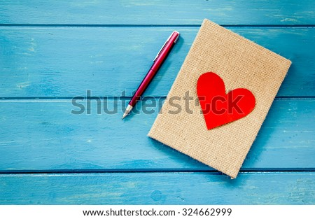 love heart on notebook with pen on blue wooden table - stock photo