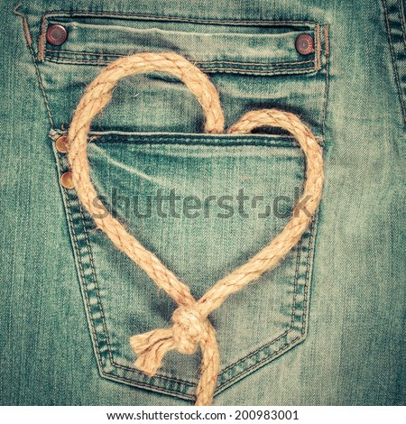 Love heart shaped rope on denim jeans pocket background. Valentine's day card concept - stock photo
