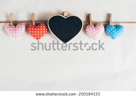 Love hearts hanging on wooden texture background, valentines day card concept - stock photo