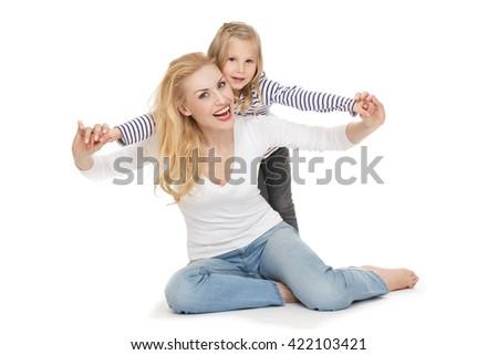 Love her little angel. Portrait of a cheerful adult woman playing with her little daughter at the studio looking to the camera smiling on white background. - stock photo