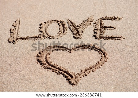 Love holiday. Painted heart on beach sand - stock photo