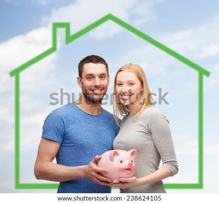 love, home, people and family concept - smiling couple holding piggy bank over green house and blue sky with grass background - stock photo