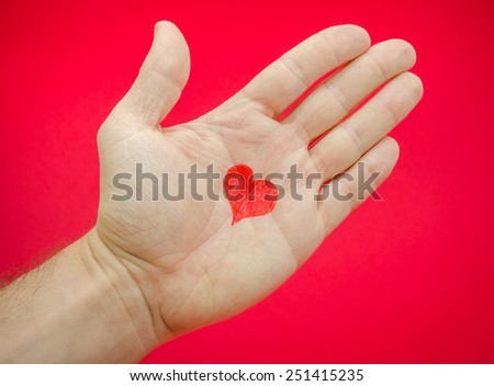 Love in a man's hands with lots of feelings and emotions from a relationship or health care concept suggested by a heart drawn on a palm over a red background - stock photo