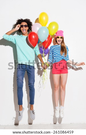 Love in all the colors of rainbows. Funky young couple holding balloons while jumping against white background - stock photo