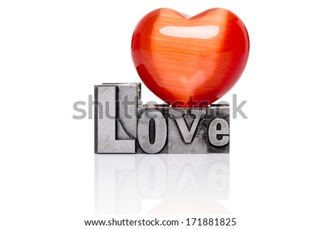Love in old mixed font metal letterpress blocks with a red gemstone heart on top, isolated on a white background. - stock photo