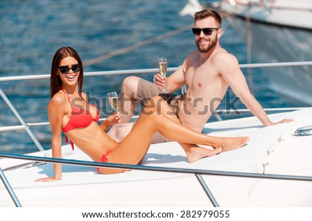 Love in the sunshine. Cheerful young couple holding glasses with champagne while sitting on the deck of yacht  - stock photo