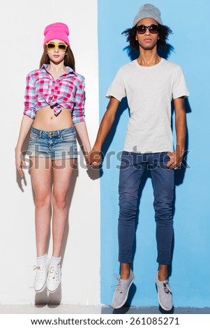 Love inspires. Funky young couple wearing sunglasses and smiling while jumping against colorful background - stock photo