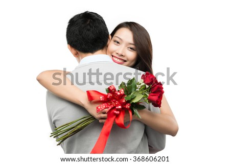 Love is a great feeling! Beautiful young loving couple bonding to each other while woman hugging her boyfriend holding bouquet of flowers - stock photo