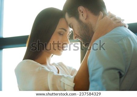 Love is in the air. Beautiful young loving couple bonding to each other while woman embracing her boyfriend - stock photo