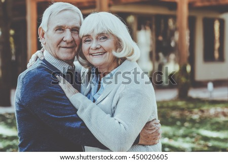 Love is in the air. Happy senior couple bonding to each other and smiling while standing outdoors and in front of their house - stock photo