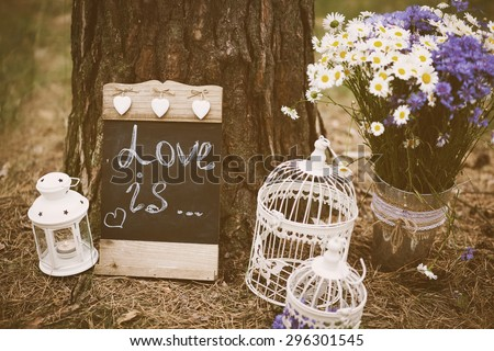 Love is - inscription for wedding. Wedding decor. Image toned in retro style. - stock photo