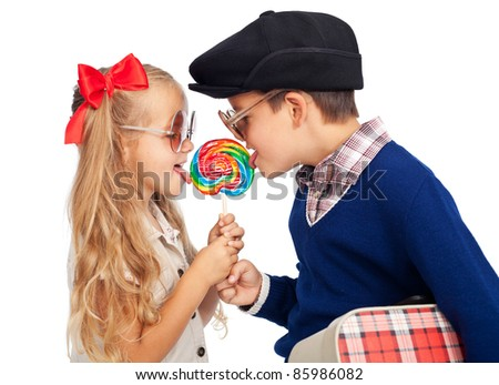 Love is sharing - childhood sweethearts with a lollipop and vintage clothes - stock photo