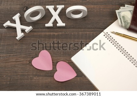 Love Kiss Concept. Sign XOXO, Two Paper Pink Sticker Hearts, Gold Pen, Blank Page, Male Wallet With Dollar Cash On The Wood Background With Copy Space, Top View - stock photo