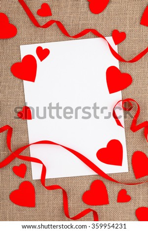 Love letter on a desk with red hearts and ribbon. Happy Valentine's Day. White piece of paper. Copyspace. - stock photo