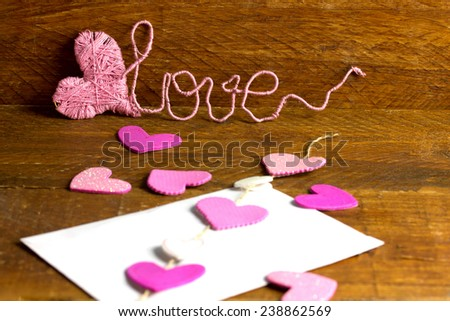love letter with pink and white hearts and a text love in the background - stock photo