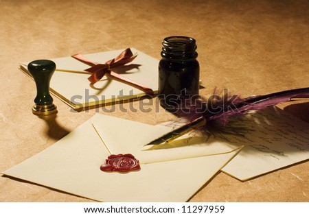 Love letters with a quill, an inkwell & a stamp on a rustic paper. - stock photo