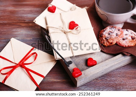 Love letters with coffee and cookies on wooden background