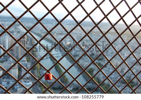Love Lock in france. Love Lock shown on a public barricade, with Paris France and river Seine in the background. - stock photo