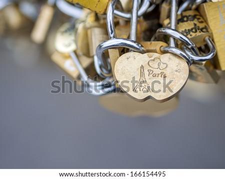Love locks in Paris France bridge symbol of friendship and romance - stock photo