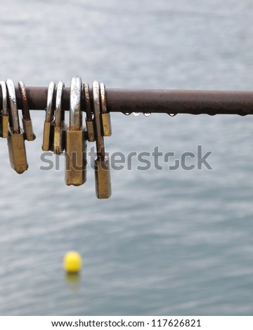 Love locks on rainy day with  grey sea background