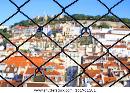 Love locks on the grate of the elevator Santa_Justa in Lisbon with blurred city view on the background - stock photo