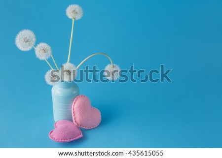 Love message concept. Light dandelions and heart on blue background with copy space - stock photo