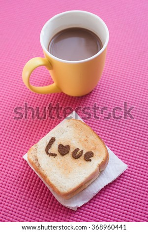 Love message on Bread sliced with and chocolate cup on pink yoga mat.  Valentine concept.