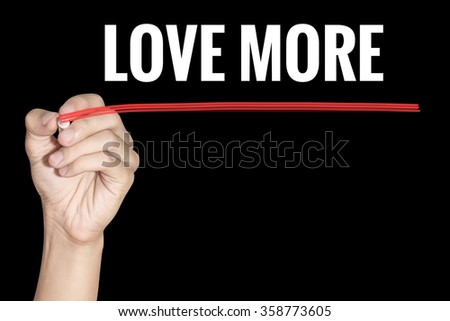 Love More word writing by men hand holding red highlighter pen on dark background - stock photo
