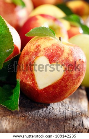 Love of apples concept with a neatly incised heart in the skin of a ripe red apple on an old weathered wooden table - stock photo