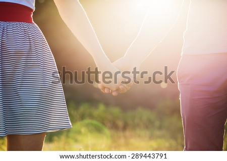 Love of man and woman: two hands over sun ray and nature - stock photo