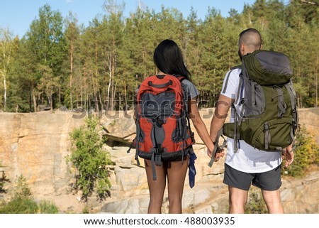 Love of nature brings them closer. Shot of a young couple with backpacks exploring outdoors enjoying the view of a mountain holding hands copyspace on the side