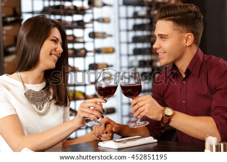 Love of youth. Beautiful young loving couple smiling and toasting wine glasses on a romantic date at the restaurant